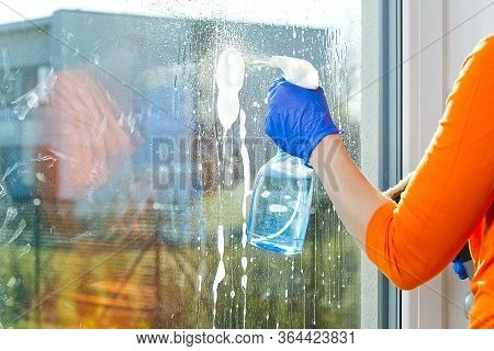 Spring Washing Of A Dirty Window. Service For Washing Windows In Domestic Homes. A Woman In Blue Glo