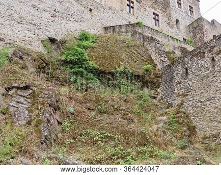 Part Of Uncovered Natural Rock On Which The Medieval Castle Of Vianden Stands. Stone, Green Plants,
