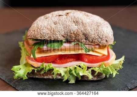 Sandwich With Ham And Vegetables Close-up. A Sandwich With A Square Loaf Of Dark Bread.