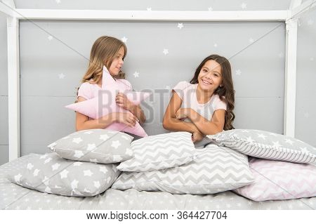 Happy Childhood. Happy Children Have Fun In Bed. Little Girls Play With Cushions. Enjoying Childhood