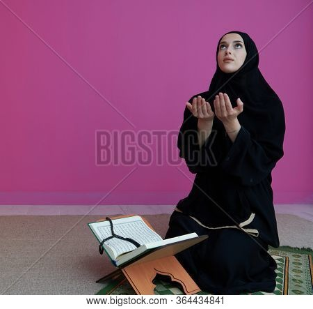 Sarajevo, Bosnia and Herzegovina - May 28, 2019 woman praying and reading the holy Quran (public item of all muslims). Education concept of Muslim woman studying The holy Quran at home