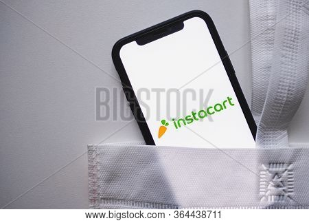 Instacart App Logo On The Smartphone Screen With White Shop Eco Bag.
