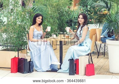 Two Beautiful Young Women Having Coffee At Restaurant. Coffee Break After Shopping. Two Women Have F