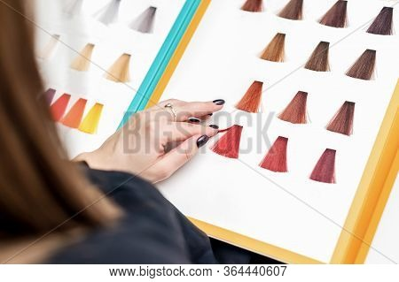 Close Up Of Clients Hand Choosing Color From Hair Samples In Salon. Customer Choosing Colour For Her