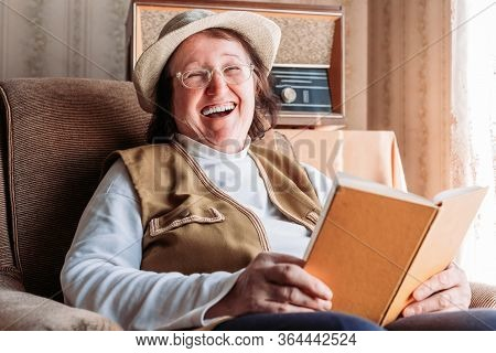 Elderly Woman With A Hat On, Reading A Book By The Window. Laughing, Felling Happy. Afternoon Light