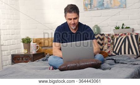 Stay at home and work in home office - Casual man sitting on bed working online from home with laptop computer.