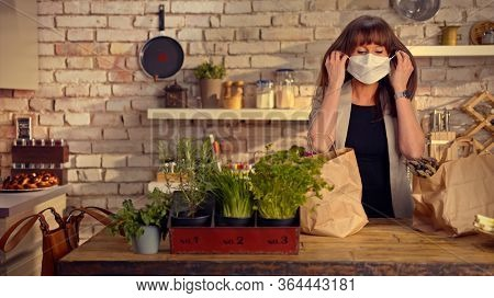 Covid-19 situation - Woman taking off face mask in the kitchen unpacking grocery bags full of vegetables arriving home from shopping.