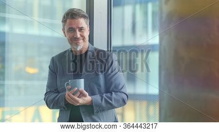 Happy older businessman taking break in office drinking coffee standing in window and daydreaming, thinking.