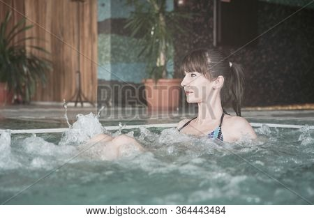 Wellness - white woman in her 30s taking bath in pool, smiling. Wellness whirlpool water, Pastel colors.