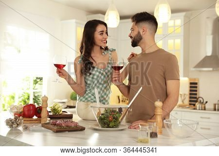 Lovely Young Couple Drinking Wine While Cooking Together At Kitchen