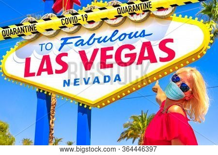Woman With A Surgical Mask During Covid-19 Pointing Welcome To Fabulous Las Vegas Nevada Sign. Nevad