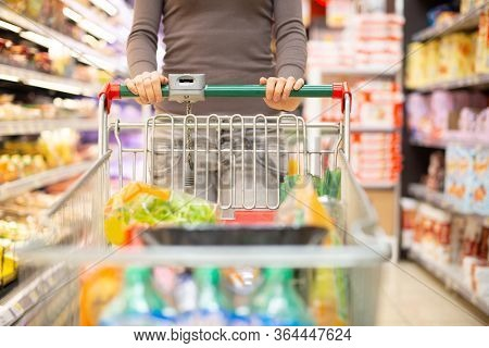 Woman pulling a shopping cart in a grocery store