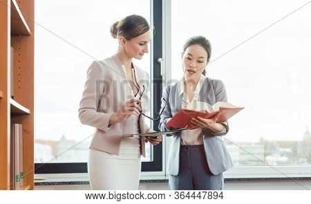 Asian and European lawyer in their law firm working reading legal books