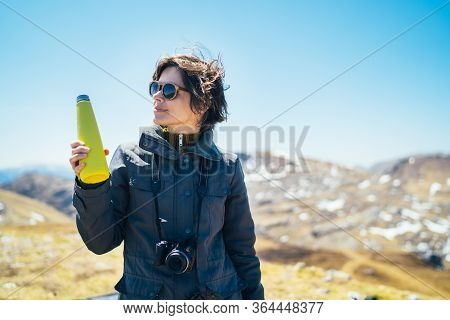 Young Woman Spending Free Time In National Park/mountains.hiking Outdoor Experience.drinking From Re