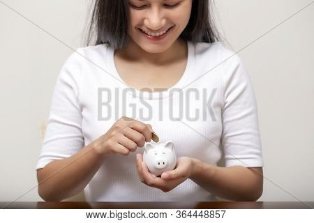 Happy Female Hand Putting Money Into Piggy Bank For Saving Money,
