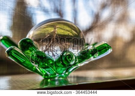 Close Up Of The Glass Souvenir Figurine Placed On The Window With The Tree Outside Reflected In The