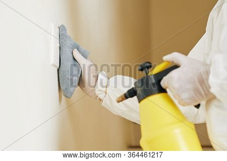 Technician In Protective Suit Wiping Frequently Touched Switch On The Wall To Stop Spread Of Coronav