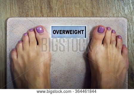 Top-down View Female Bare Feet Standing On Scale With Written Word Overweight On Display. Concept Of