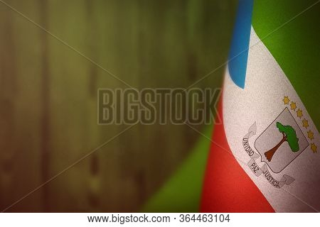 Equatorial Guinea Hanging Flag For Honour Of Veterans Day Or Memorial Day On Green Blurred Natural W