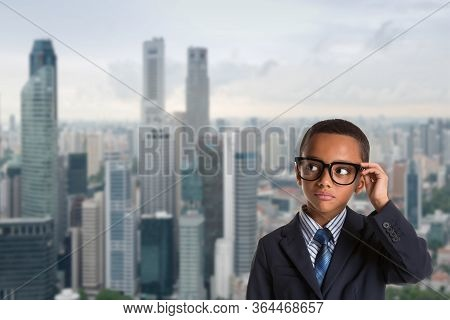 Concept Of Leadership And Success - Thoughtful African American Boy In Business Suit With Glasses Ov