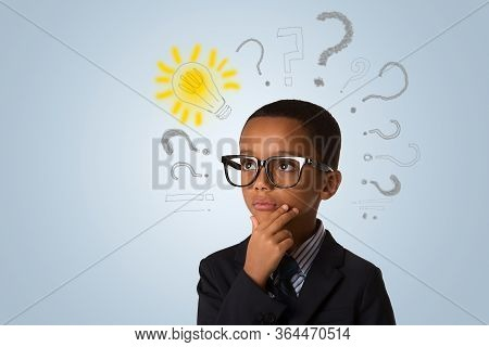 Adorable African Little Boy Wearing Glasses And Thinking With Many Question Marks And Lightbulb. Con