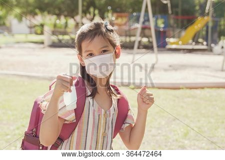 Mixed Asian Girl Wearing Mask And Holding Hand Sanitizer Near Playground, School Reopening, Return B