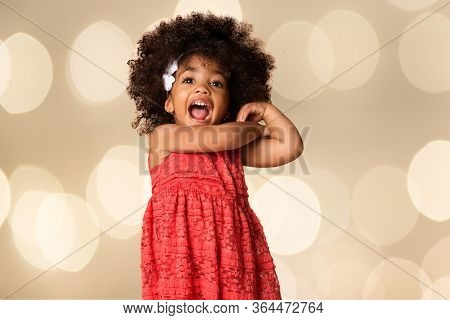 Portrait Of Cheerful African American Little Girl Over Blurred Lights Background