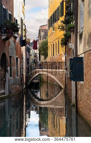 Street With Canal, Small Bridge And Reflections In Venice, Italy.