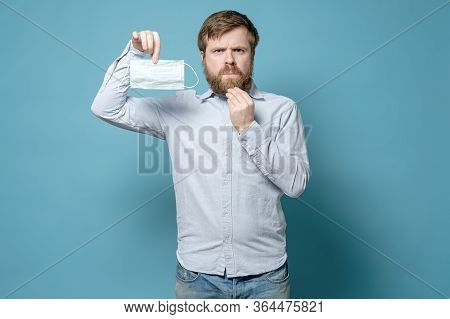 Caucasian Man Is Displeased Because A Shaggy Beard Will Create Problems When Wearing A Medical Mask.