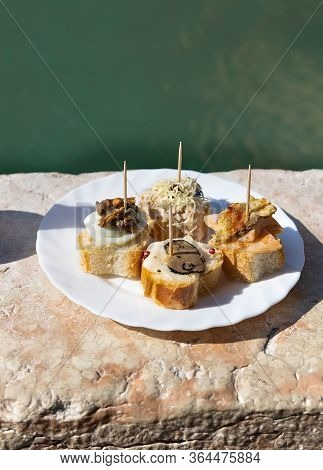 Traditional Venetian Appetizers Cicchetti On Turquoise Green Water Of Canal Background. Venice, Ital