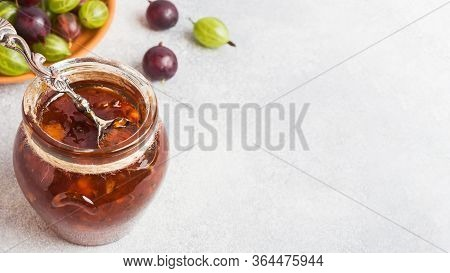 Gooseberry Jam In A Jar With Fresh Gooseberry Berries On A Gray Background. Copy Space.