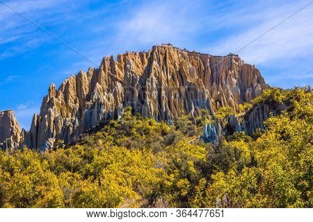 Fabulous faraway country. New Zealand. Colossal clay peaked outliers - Clay Cliffs in the hills separated by narrow ravines. South Island. The concept of exotic, extreme, natural and photo tourism
