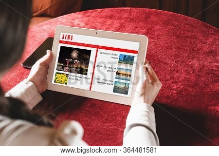 Woman Reading The News On The Tablet