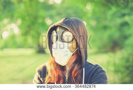 Woman wearing old hazmat style gas mask and medical mask, outside in bright summer environment.