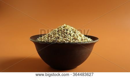 Raw Green Buckwheat In A Brown Clay Plate On A Brown Background. Vegan Organic Food Concept. The Con