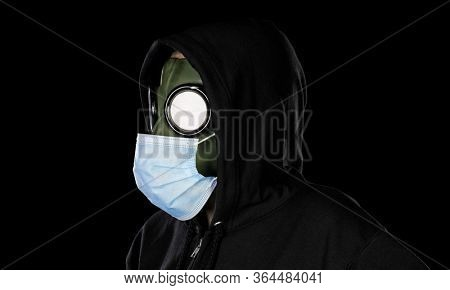 Person wearing old retro hazmat style gas mask and medical mask