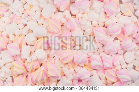 Marshmallow. Close-up of various colourful Marshmallows colorful chewy candy backdrop, colorful pink with white and yellow background. Sweet food dessert backdrop, closeup. Top view, flatlay.