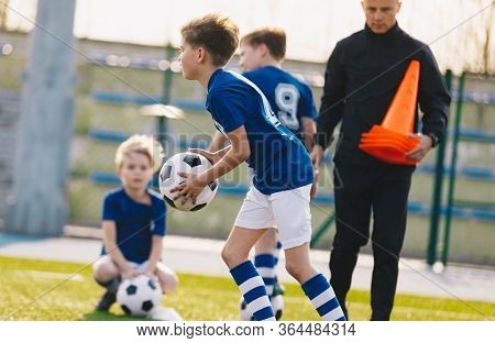 Kids Junior Football Training Session. Soccer Training For Kids. Young Boys Practicing Football With