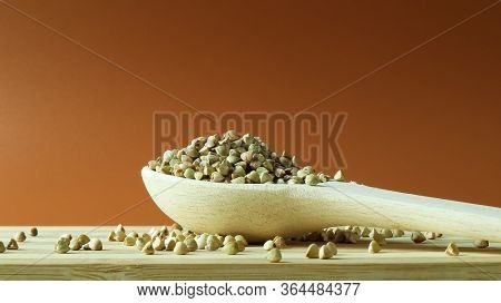 Green Buckwheat In A Wooden Spoon On A Brown Background. Great Food. Healthy Groats. Organic Raw Non