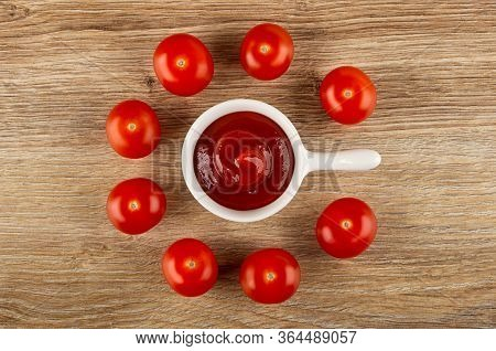 Few Tomato Cherry And Ketchup In Small Sauceboat With Handle On Wooden Table. Top View