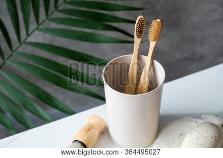 Eco Friendly Wooden Toothbrushes In Glass On Bathroom Table. Natural Bamboo Toothbrushes For Dental