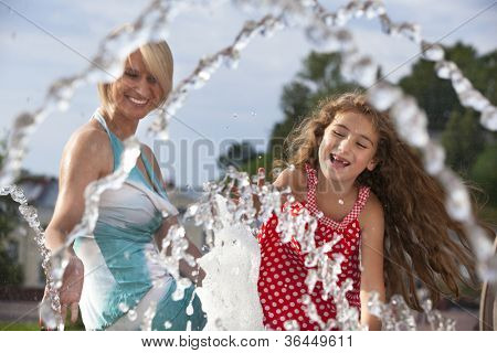 Mother and baby daughter in with water playing in the founta poster