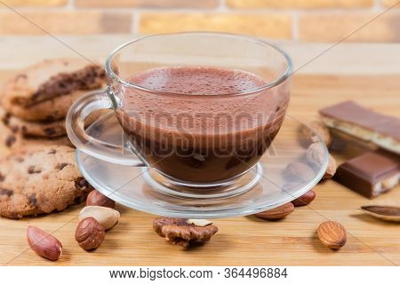 Foamed Hot Chocolate In Glass Cup On Saucer Among The Confections And Various Nuts Close-up In Selec
