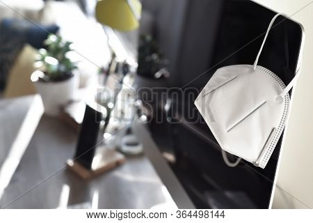 Home Office With Face Mask Representing Work  From Home During Period Of Isolation And Social Distan