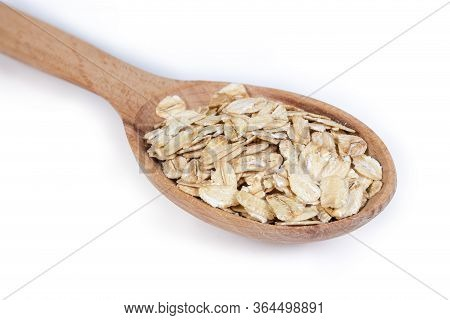 Uncooked Rolled Oats In The Wooden Spoon On A White Background, Close-up In Selective Focus