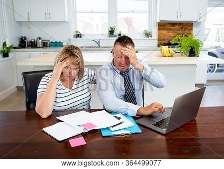 Coronavirus Economic Recession. Family Couple With Masks In Distress Over Home Finances And Small Bu