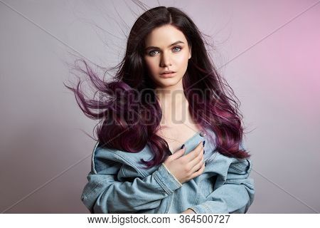 Portrait Of A Woman With Bright Colored Flying Hair, All Shades Of Purple. Hair Coloring, Beautiful