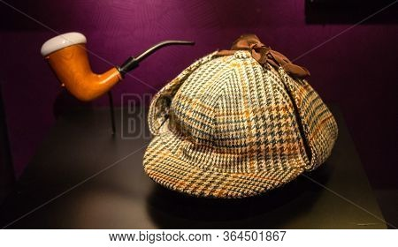 A Houndstooth Deer Stalker Hat And A Briar Pipe Made Famous By Fictional Detective, Sherlock Holmes