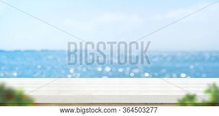 Empty White Plank Wood Table With Blur Blue Sky And Sea Bokeh Background With Green Leaf Foreground,
