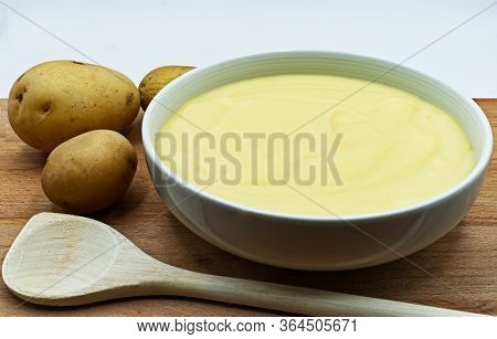 A Bowl Of Mashed Potatoes Puree, With Raw Potatoes And Wooden Spoon.